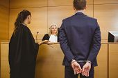 stock photo of court room  - Judge talking with the criminal in handcuffs in the court room - JPG