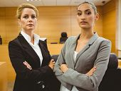foto of court room  - Two serious lawyers standing with arms crossed in the court room - JPG