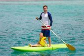 image of paddling  - Father and his adorable little daughter paddling on stand up board having fun during summer beach vacation - JPG