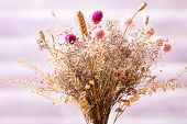 foto of vase flowers  - Bouquet of dried flowers in vase on color planks background - JPG