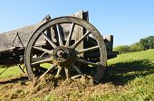stock photo of wagon wheel  - An old rickety wooden wagon with a large wheel with wood spokes was used for carrying merchandise is parked in grass - JPG
