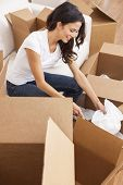 picture of single woman  - A beautiful single young woman packing or unpacking boxes and moving into a new house or home - JPG