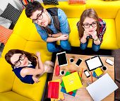 stock photo of nerd  - Three nerds in eyeglasses sitting on the couch and looking at camera with different gadgets on the background - JPG