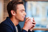 pic of toothless smile  - Side view of handsome young man keeping eyes closed and smiling while smelling cup of fresh coffee in cafe - JPG