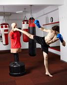 pic of kickboxing  - Kickboxer executing a kick on the dummy in the gym - JPG
