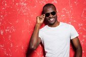 stock photo of shot glasses  - Cheerful young African man adjusting his glasses and smiling while standing against red background - JPG