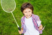 pic of shuttlecock  - Top view of happy little boy holding badminton racket and shuttlecock while standing on green grass