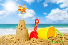 picture of spade  - Sandcastle with bucket and spade with beach blur background - JPG