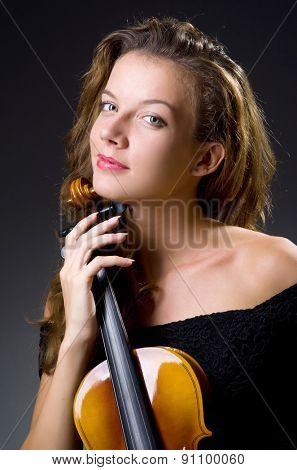 Female musical player against dark background