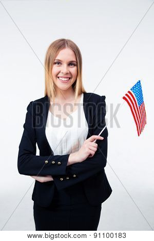 Smiling young businesswoman holding US flag isolated on a white background. Looking at camera