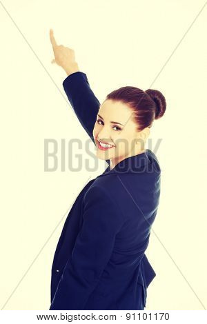 Businesswoman pointing on copy space.