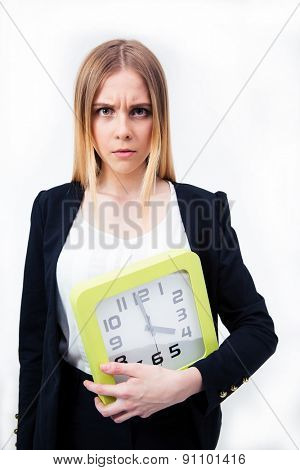 Serious businesswoman holding big clock over gray background and looking at camera