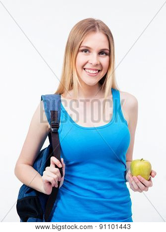 Happy female student holding green apple and backpack over gray background. Looking at camera