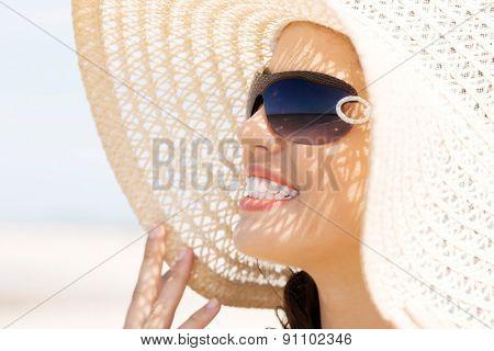 Portrait of a woman wearing hat sunbathing.