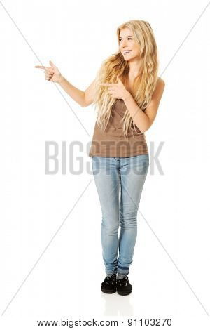 Full length student woman pointing to the right.