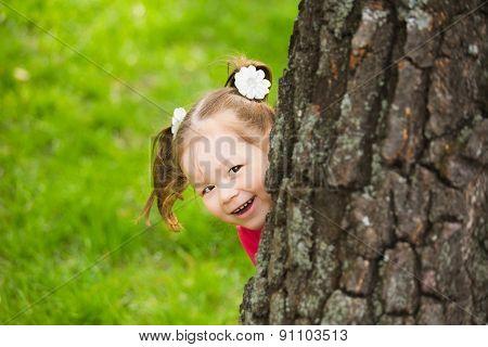 Cute Little Girl Hiding Behind Huge Tree