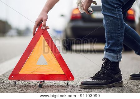 car with breakdown alongside the road, man sets warning triangle