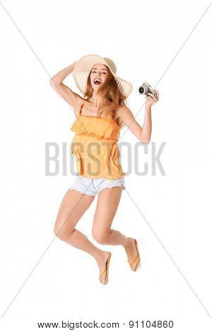 Jumping woman holding a camera.