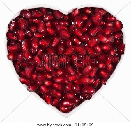 Pomegranate Seeds In Plate In The Form Of Heart On A White