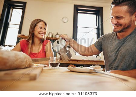 Smiling Young Couple Having Breakfast Together In Kitchen
