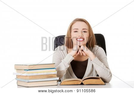 Woman sitting at the desk full of books.