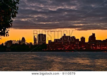 Looking Over The River Thames Towards Wapping And The City, At Sunset With Low Passing Clouds, Londo