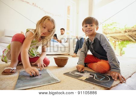 Children Drawing While Their Father In Background