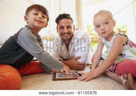 Family Sitting On Floor Using Digital Tablet