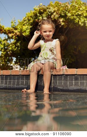 Cute Little Girl Sitting On The Edge Of A Swimming Pool