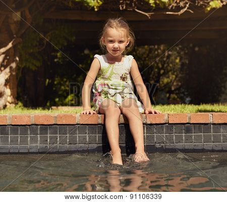 Adorable Little Girl Enjoying Sitting By Edge Of Pool