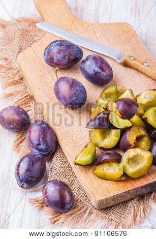 Sliced Fresh Ripe Plums On A Wooden Cutting Board