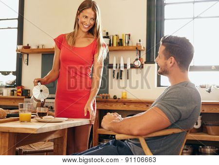 Happy Young Couple In Kitchen At Breakfast Table
