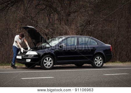 Upset man checking his car engine after breaking down