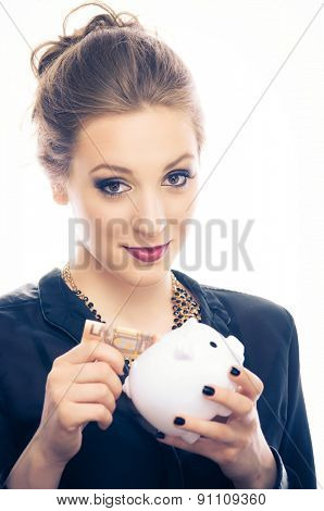 Young woman put 50 euro banknote in a piggy bank, isolated on white