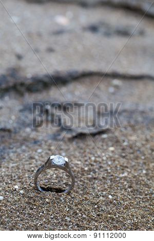 Wedding ring as symbol laying on the beach sand