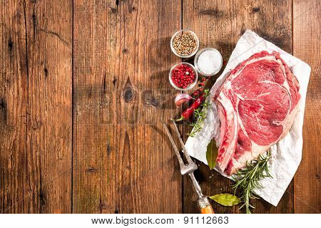 Raw fresh meat rib eye steak and seasoning on wooden background