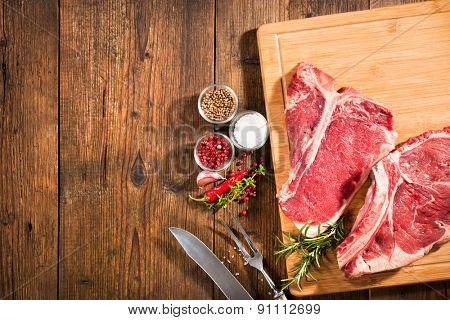 Raw fresh beef steaks and seasoning on wooden background
