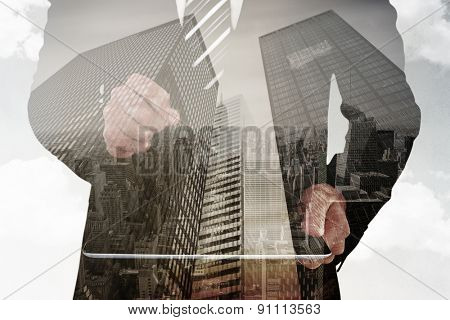 Businessman looking at tablet with magnifying glass against low angle view of skyscrapers