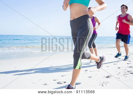 Friends doing jogging together at the beach