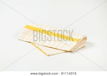 white and yellow checkered dishtowel on white background