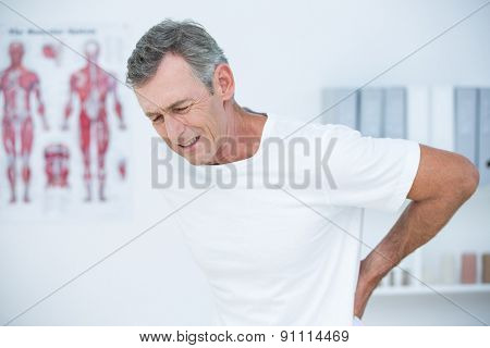 Suffering patient touching his back in medical office