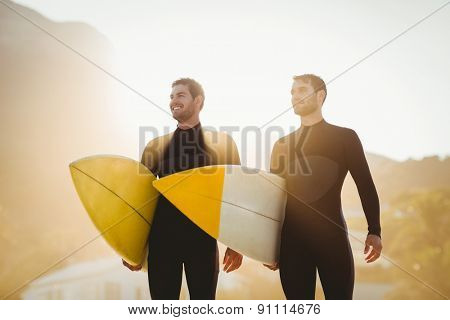 Two men in wetsuits with a surfboard on a sunny day at the beach