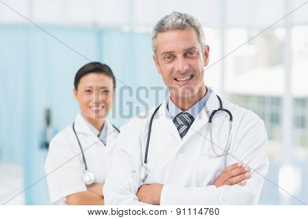 Portrait of confident male and female doctors at medical office