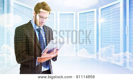 Businessman using a tablet computer against server room