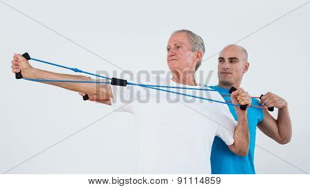 Old man stretching elastic in fitness studio