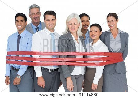 Smiling business people surrounding by red strip in office