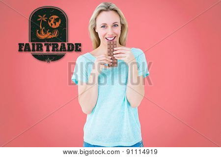 Smiling blonde eating bar of chocolate against red background