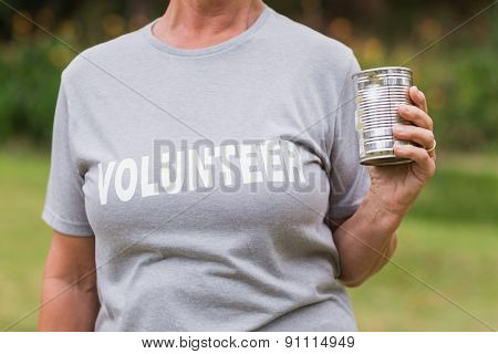 Volunteer holding tin can on a sunny day