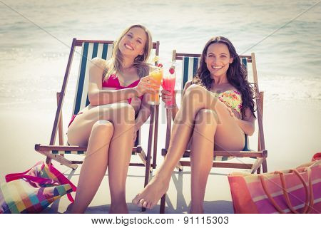 Cute friends having cocktails on the beach on a sunny day