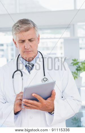 Smiling doctor holding tablet in medical office